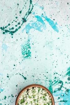 Vista dall'alto di insalata di cavoli affettati freschi con verdure all'interno di una ciotola marrone su uno spuntino di freschezza di insalata di verdure di cibo blu e verde brillante