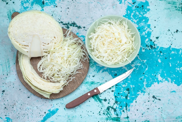 Vista dall'alto di cavoli affettati freschi con mezza verdura intera sulla scrivania blu brillante, insalata sana spuntino pasto di cibo vegetale