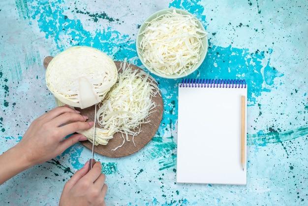 Vista dall'alto di cavoli affettati freschi con metà verdura intera che viene tagliata e blocco note sulla scrivania blu brillante, insalata sana spuntino pasto vegetale