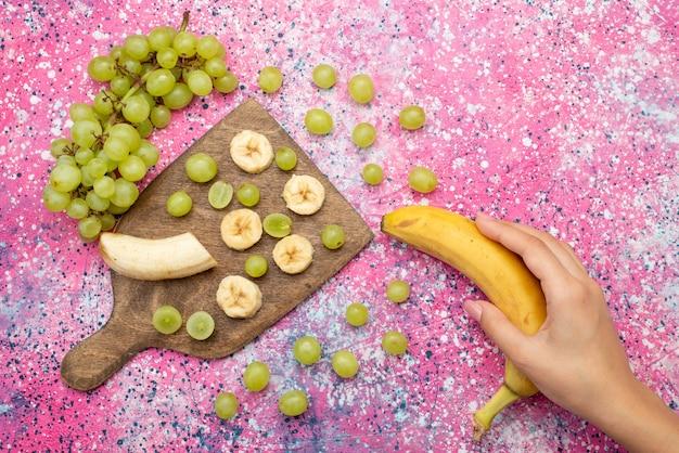 Вид сверху свежих нарезанных фруктов, винограда и бананов на фиолетовом столе, цвет фруктов, витамин