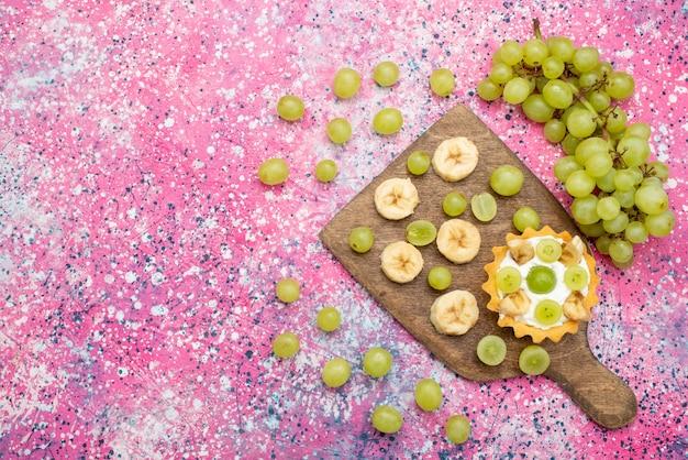 Вид сверху свежих нарезанных фруктов, винограда и бананов с кремовым пирогом на фиолетовой поверхности, фруктовый мягкий цвет, витамин