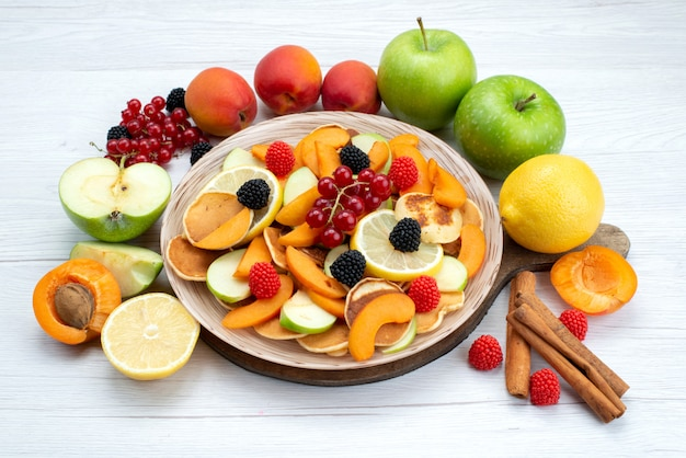 A top view fresh sliced fruits mellow with cinnamon and whole fruits on the wooden desk and white background fruits color food photo