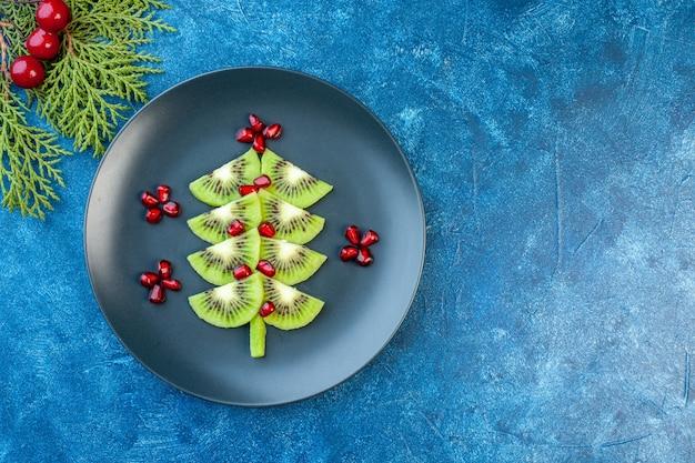 Vista dall'alto kiwi affettati freschi con melograni all'interno del piatto su sfondo blu