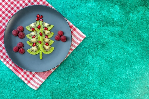 Top view fresh sliced kiwis with raspberries on green background