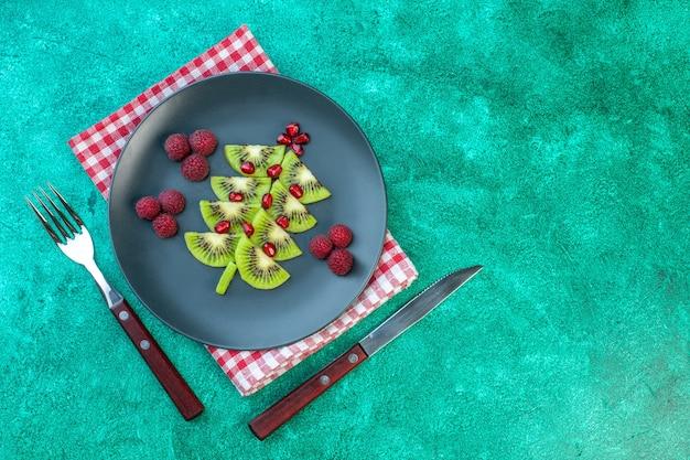 Kiwi freschi affettati vista dall'alto con lamponi all'interno del piatto su sfondo verde