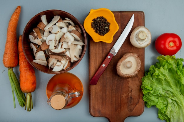 Top view of fresh sliced mushrooms in a bowl and whole mushrooms with kitchen knife and black peppercorns on a wood cutting board