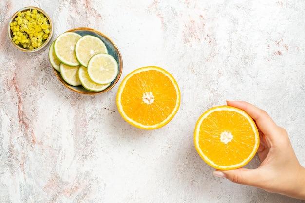 Vista dall'alto arancia fresca affettata con limone su sfondo bianco colore frutta succo fresco agrumi