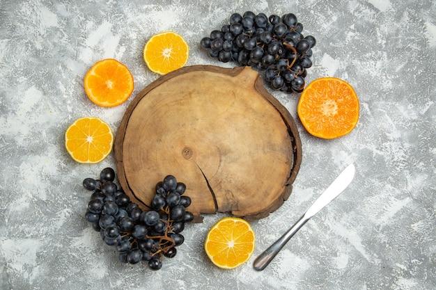 흰색 표면 감귤 주스 익은 신선한 과일에 검은 포도와 함께 상위 뷰 신선한 슬라이스 오렌지