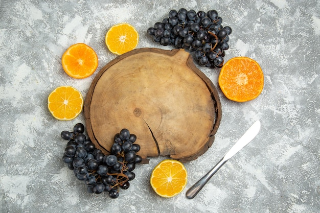 Top view fresh sliced oranges with black grapes on white surface citrus juice ripe fresh fruit