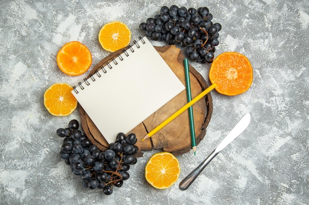 Top view fresh sliced oranges with black grapes on white surface fresh citrus juice ripe fruit