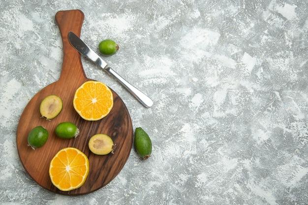 흰색 표면에 익은 과일 이국적인 열대 신선한 페이조아가 있는 신선한 얇게 썬 오렌지 무료 사진