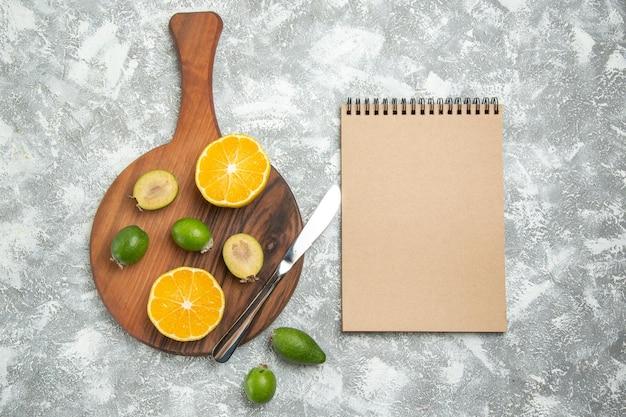 흰색 표면에 익은 과일 이국적인 신선한 열대에 페이조아가 있는 신선한 얇게 썬 오렌지