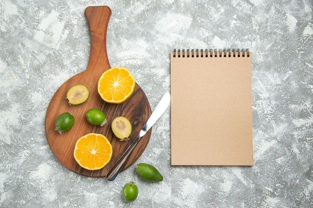 Top view fresh sliced oranges with feijoa on white surface ripe fruit exotic fresh tropical