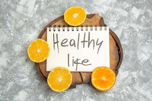 上面図新鮮なスライスしたオレンジと健康的な生活が白い表面に書かれている柑橘類のジュース熟した新鮮な果物
