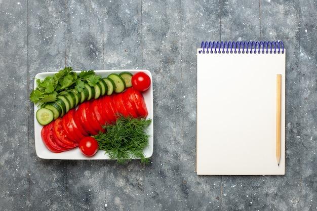 Vista dall'alto pomodori freschi affettati insalata dal design elegante sulla scrivania grigia
