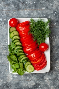 グレーのスペースにエレガントにデザインされたサラダを上から見た新鮮なスライストマト