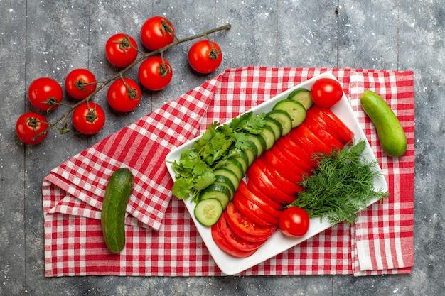 회색 공간에 샐러드를 우아하게 디자인 한 상위 뷰 신선한 슬라이스 토마토