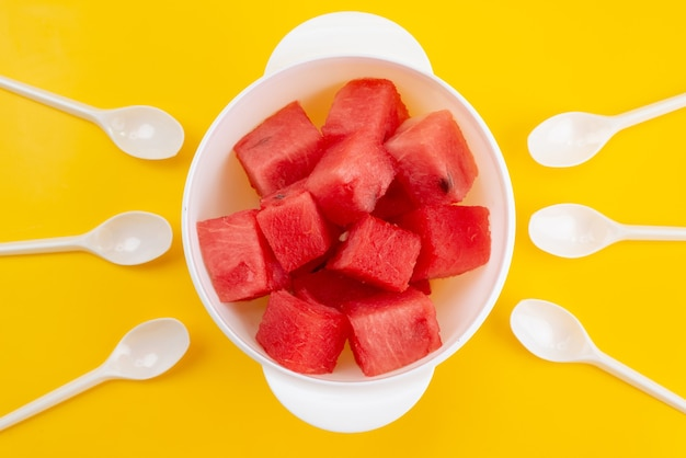 A top view fresh sliced watermelon inside white, plastic plate on yellow, fruit summer color