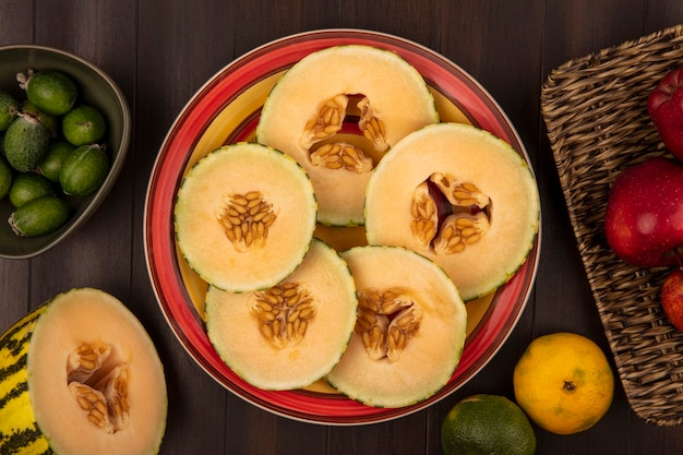 Top view of fresh slices of cantaloupe melon on a plate with feijoas on a bowl with apples on a wicker tray on a wooden background