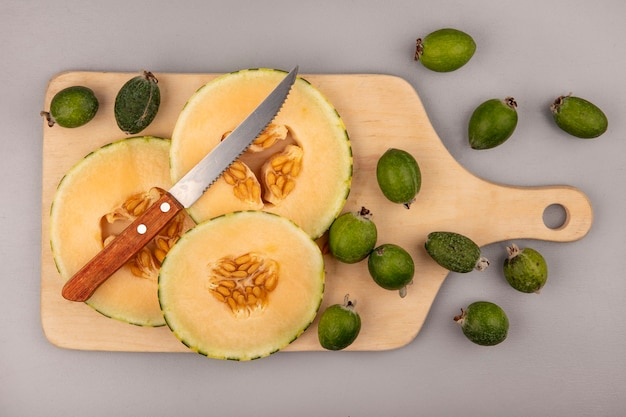 Top view of fresh slices of cantaloupe melon with feijoas isolated on a wooden kitchen board with knife on a grey wall