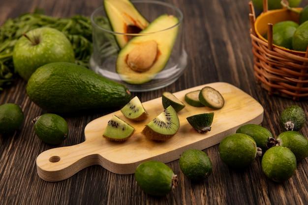 Vista dall'alto di fette fresche di kiwi su una tavola da cucina in legno con mezzo avocado su una ciotola di vetro con mele verdi feijoas avocado e prezzemolo isolato su una parete in legno