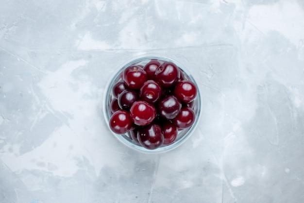 Vista dall'alto di amarene fresche all'interno della tazza di vetro sulla scrivania bianco-chiaro, foto di vitamine delle bacche acide della frutta