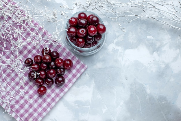 Vista dall'alto di ciliege acide fresche all'interno di una piccola tazza di vetro sul pavimento leggero frutta bacche acide vitamina
