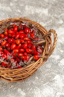 Vista dall'alto di cornioli freschi aspri all'interno del cestello sulla superficie bianco-chiaro frutti berry vitamina acido mellow pianta albero