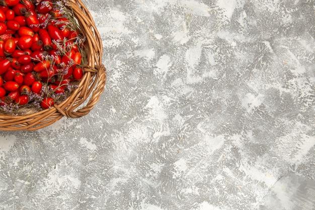 ライトホワイトの背景にバスケット内の新鮮な酸っぱいハナミズキの上面図フルーツベリービタミン酸っぱいまろやかな植物の木野生