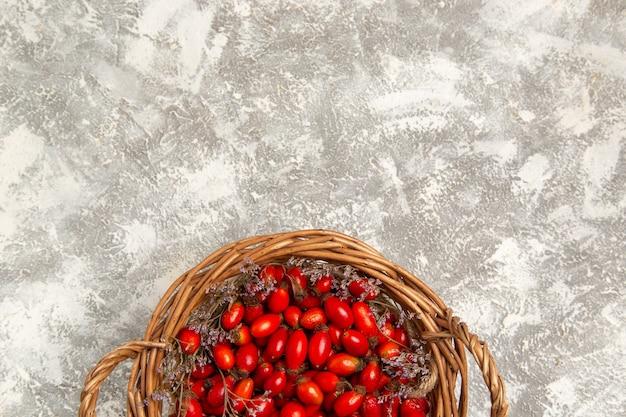Вид сверху свежие кислые кизилы внутри корзины на белом столе фруктовые ягоды витамины кислые спелые растения дерево дикие