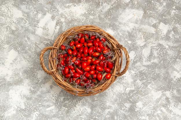 Вид сверху свежие кислые кизилы внутри корзины на белой поверхности фруктовые ягоды витамин кислые спелые растения дерево дикие