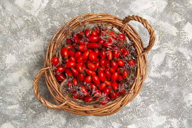 Vista superiore fresca acida cornioli all'interno del cestello sulla superficie bianca frutti berry vitamina acido dolce pianta albero selvatico