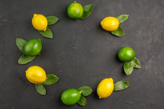 Top view fresh sour lemons on dark-grey floor lime fruit citrus