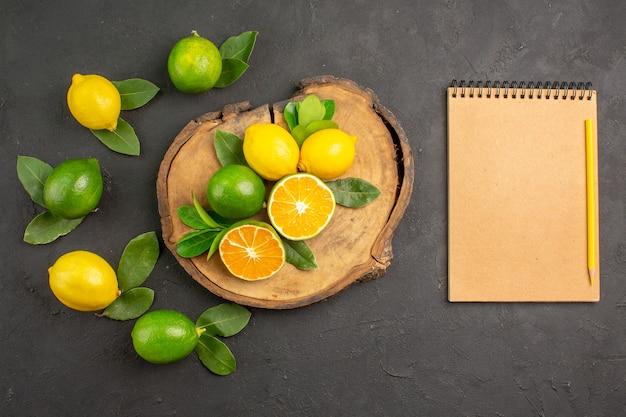 Vista dall'alto limoni freschi acida sulla calce di agrumi frutta tavolo scuro