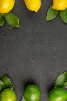 Vista dall'alto freschi limoni aspri sul tavolo scuro lime frutta agrumi maturi maturi