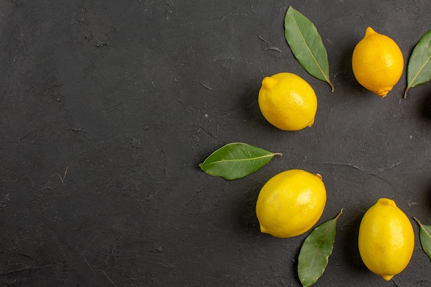 Top view fresh sour lemons lined on dark table, fruit citrus yellow lime