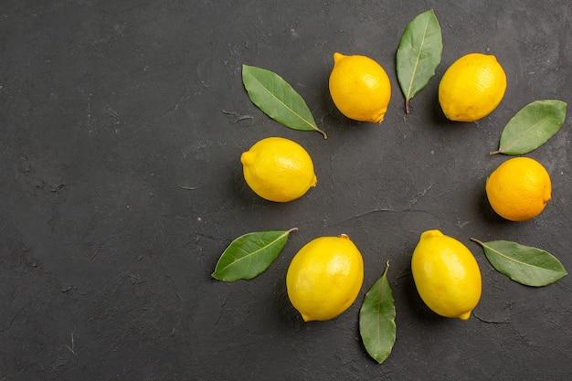 Вид сверху свежие кислые лимоны, выложенные на темном столе, фрукты, цитрусовые, желтый, лайм