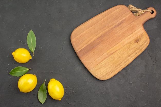 Вид сверху свежих кислых лимонов, выложенных на темном столе, фруктов, лайма, желтых цитрусовых