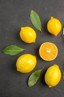 暗いテーブルに並ぶ新鮮なサワーレモン、柑橘系のライムイエローのフルーツの上面図