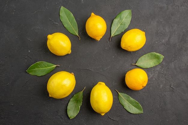 暗いテーブルに並ぶ新鮮なサワーレモン、フルーツシトラスイエローライムの上面図