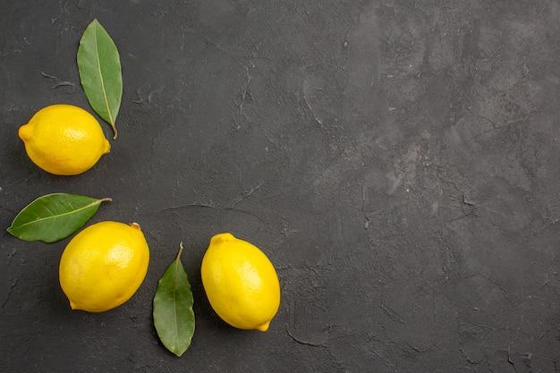Вид сверху свежие кислые лимоны, выложенные на темном столе, лайм, желтые фрукты, цитрусовые