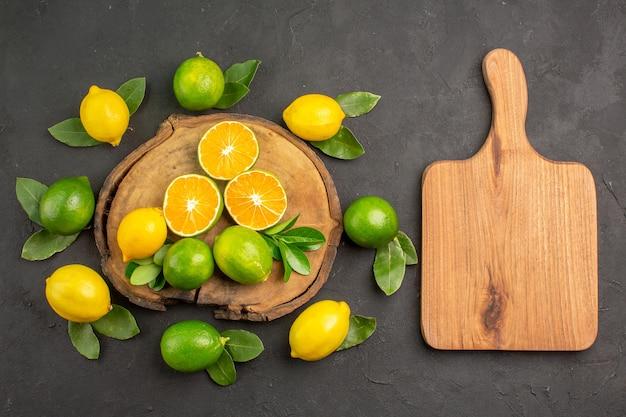 Вид сверху свежие кислые лимоны на темном столе цитрусовые, лайм