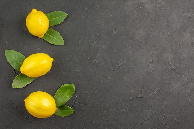 Вид сверху свежие кислые лимоны на темном столе лайм цитрусовые желтые фрукты