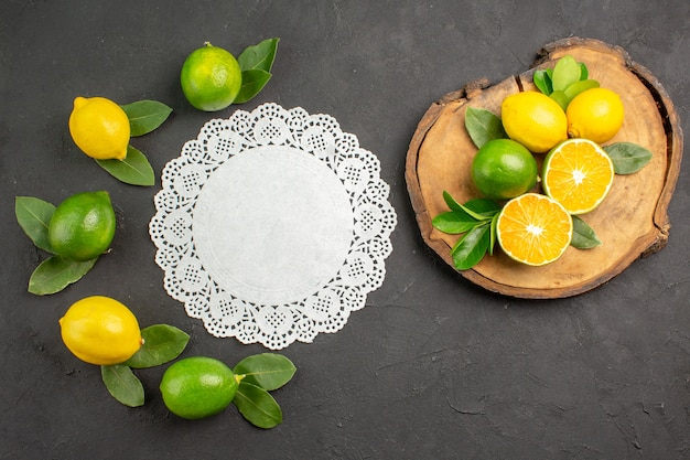 Вид сверху свежие кислые лимоны на темно-сером полу, фрукты, цитрусовые, лайм