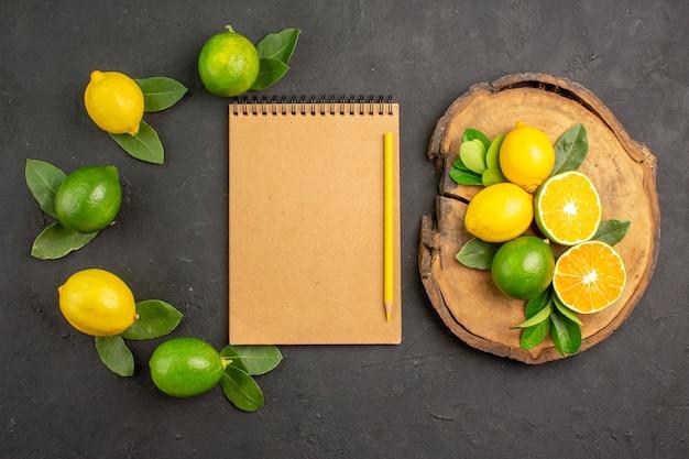 Вид сверху свежие кислые лимоны на темно-сером столовом фрукте цитрусовом лайме