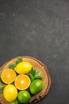 Вид сверху свежие кислые лимоны на темном столе, фрукты, цитрусовые, лайм