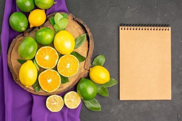 暗いテーブルの柑橘類のライムの果実の上面図新鮮なサワーレモン