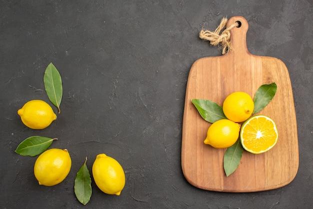 Vista dall'alto limoni freschi aspri con foglie sul tavolo scuro frutta lime giallo agrumi