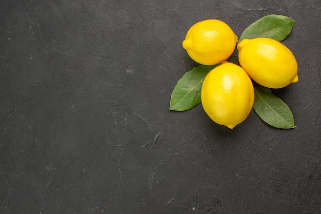 Top view fresh sour lemons with leaves on dark table lime yellow citrus fruit