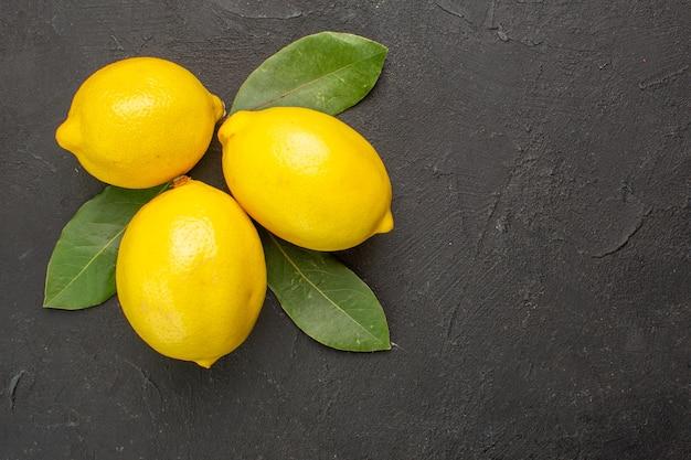 Vista dall'alto limoni freschi aspri con foglie sugli agrumi giallo lime tavolo scuro